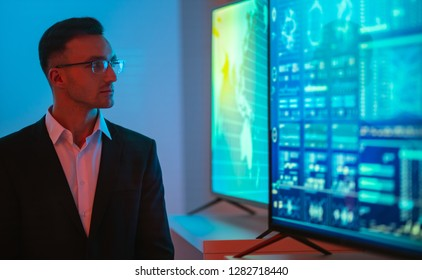 The businessman in glasses standing near big displays with graphs