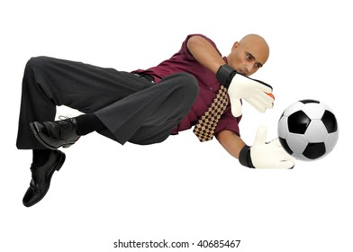 Businessman goalkeeper with gloves and ball in a acrobatic save isolated in white