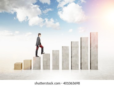 Businessman going up stairs shaped by concrete blocks. Sky at background. Concept of career growth.