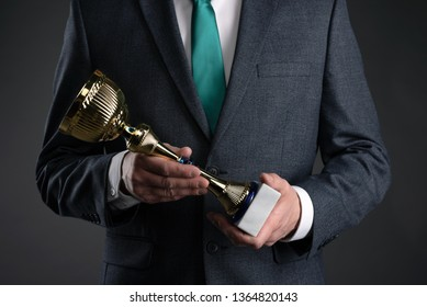 Businessman with a golden cup award trophy in hand. First place concept background. Best worker award. Business achievement.