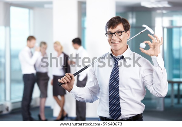 Businessman with a golf club against the staff office