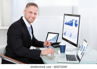Businessman with good performance graph sitting at his desk with statistical reports spread over three monitors cheering and clasping his fists