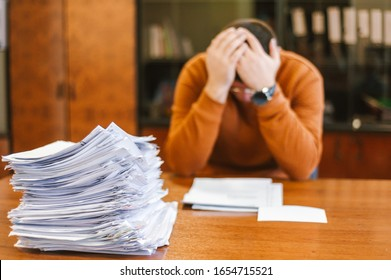 A businessman grabs his head from a pile of papers at work. The concept of depression from difficulties and possible bankruptcy of an enterprise.
