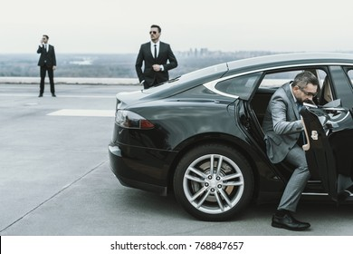 businessman in gray suit going out from black car