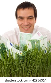 Businessman with green banknotes in grass - environmental friendly business concept, focus on money, isolated