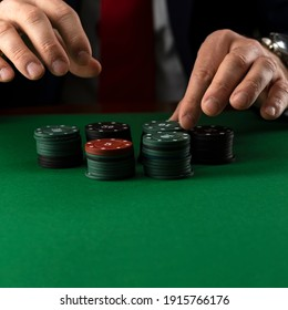 Businessman at green gaming table with casino chips.