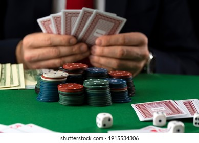 Businessman at green playing table with gambling chips and cards playing poker and blackjack in casino