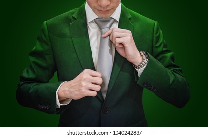 Businessman in green suit tying necktie, on dark green background. Environmental and agriculture business