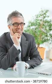 Businessman with grey hair, wearing grey suit and glasses thinking over laptop computer, sitting at desk, smiling.