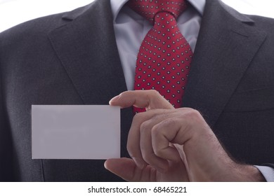 Businessman in grey suit and a blue shirt with a red power tie, shows professional business card with copy space, shallow dept of field