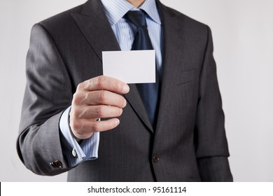 Businessman in grey suit and a blue shirt with a blue tie, shows business card with copy space, shallow dept of field, isolated on a grey background