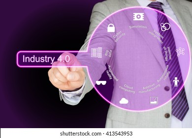 Businessman in grey suit pressing a purple button which shows a circle with the nine pillars of Industry 4.0