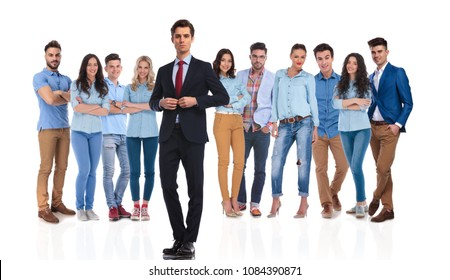 businessman group leader buttoning suit jacket in front of his casual team while standing on white background
