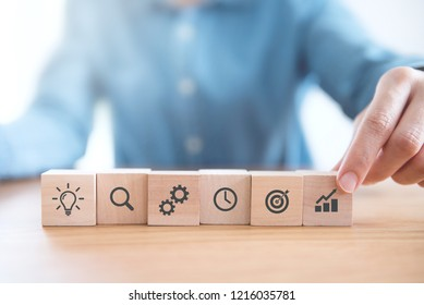 Businessman hand arranging wood block with icon business strategy and Action plan.