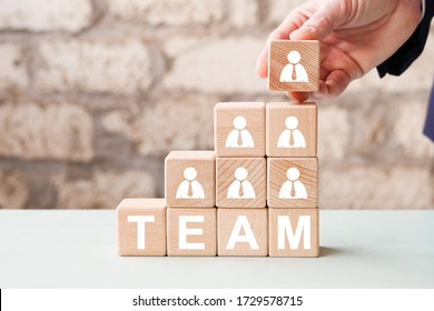 Businessman hand arranging wood block stacking with business team concept.