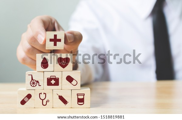 Businessman hand arranging wood block stacking with icon healthcare medical, Insurance for your health concept