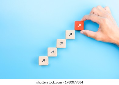 Businessman hand arranging wooden blocks stacking as step stair with arrow up, Business growth success process concept, copy space