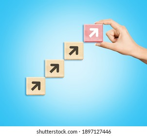 Businessman hand arranging wooden blocks stacking as step stair with arrow up,