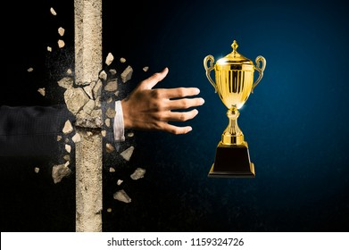 businessman hand breaking through the wall to grab a golden trophy, reward for one who has determination to succeed and do not give up on problems