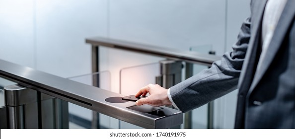 Businessman hand with business wear using smartphone to open automatic gate machine in office building. Working routine concept