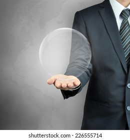 Businessman hand carrying empty transparent ball or globe - can put your objects or texts inside