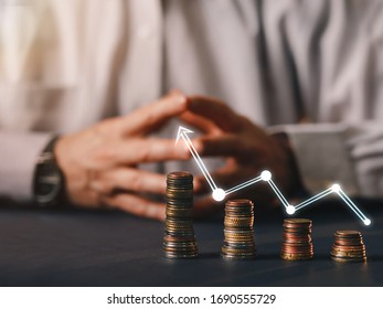 Businessman hand chasing  arrow up on money coin stack arranged as a graph. Concept of money growth and saving money with  copy space.