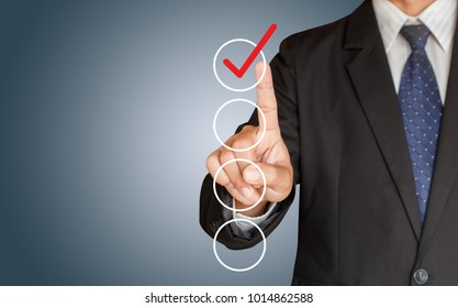 Businessman hand checking the checklist boxes on blue background