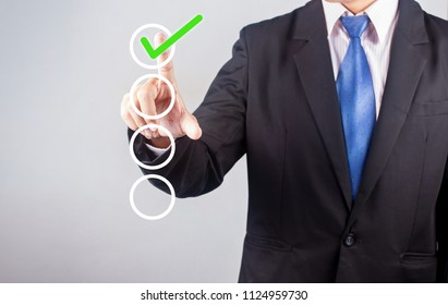 Businessman hand checking the checklist boxes on gray background