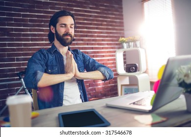 Businessman with hand clasped doing yoga in creative office