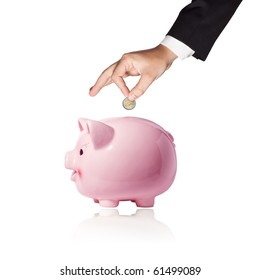 Businessman hand with a coin over a pink piggy bank on white background