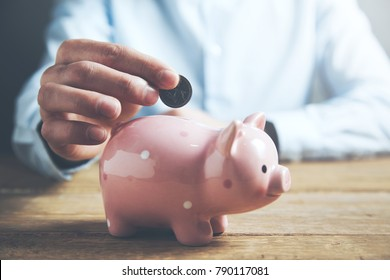 businessman hand coin and piggy bank