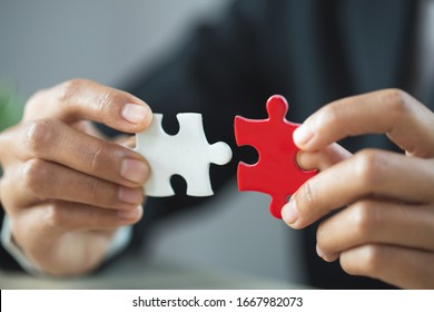Businessman hand connecting jigsaw puzzle, Business solutions,  target, success, goals and strategy concepts