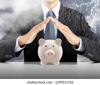 businessman hand cover pink piggy ceramic bank with heavy rain storm background, insurance