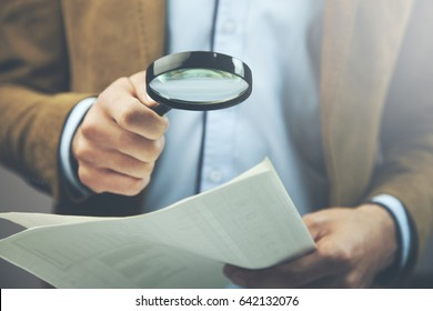 Businessman hand document and magnifier in office