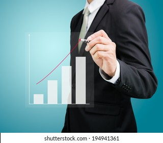 Businessman hand drawing a graph Isolated on blue background