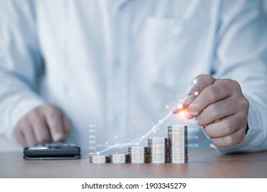 Businessman hand drawing virtual increasing graph with money coins stacking , Business investment profit and deposit dividend saving growth in 2021 concept.