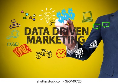 businessman hand drawing and writing DATA DRIVEN MARKETING on yellow background , business concept , business idea