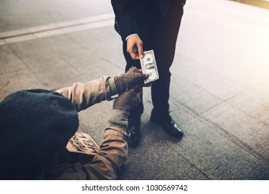 Businessman hand giving dollar to homeless beggar on the bridge.