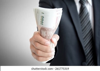 Businessman hand grabbing money, Thai Baht (THB)