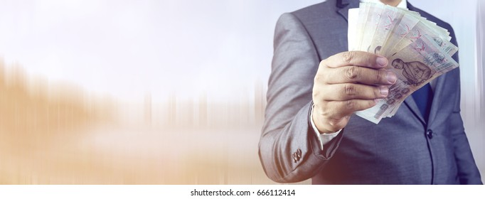 Businessman hand grabbing money, Thai Baht (THB). Concept of finance success. web banner with copy space.