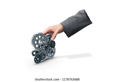 Businessman hand grabbing pile of cogwheels