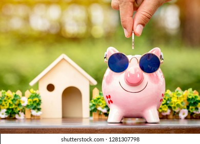 Businessman hand hold a coin is save to the piggy bank with growing a interest and wooden home model for family in the public park, Business investment and loan for real estate in the future concept.