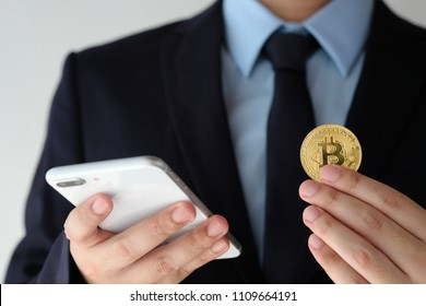 Businessman hand holding bitcoin and using smartphone over white background, blockchain and cryptocurrency concept background