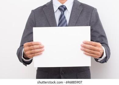 Businessman hand holding blank white board.