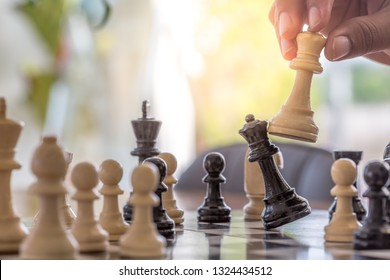 Businessman hand holding chess figure and moving in competition and strategy. Plan leading strategy of successful business competition leader concept