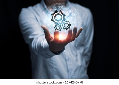 Businessman hand holding cog gear wheel infographic with sunlight. Engineering creative and business strategy concept.