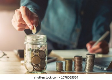 businessman hand holding coins puting into glass. concept saving money and business finance