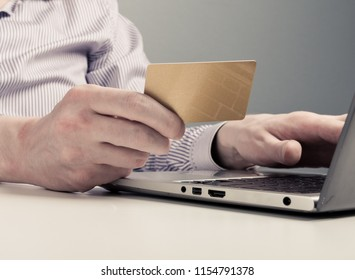 Businessman hand holding credit card and use laptop