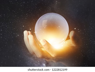 businessman hand holding crystal clear ball with galaxy universe space background