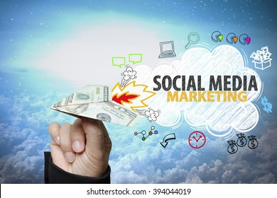 businessman hand holding dollar plane with SOCIAL MEDIA MARKETING text